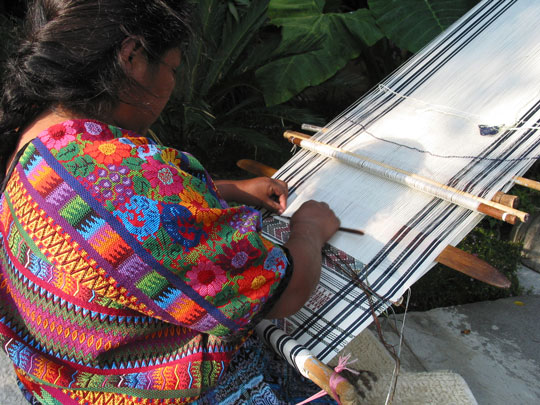 A Guatemalan woman expertly manages a traditional backstrap loom. (Photo via Kyle Johnson, CC Flickr).